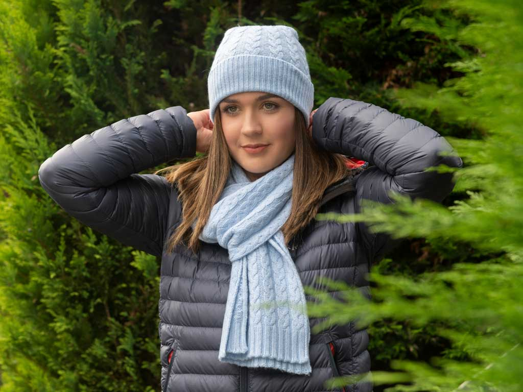 Women wearing light blue cable cashmere beanie hat and cable cashmere scarf
