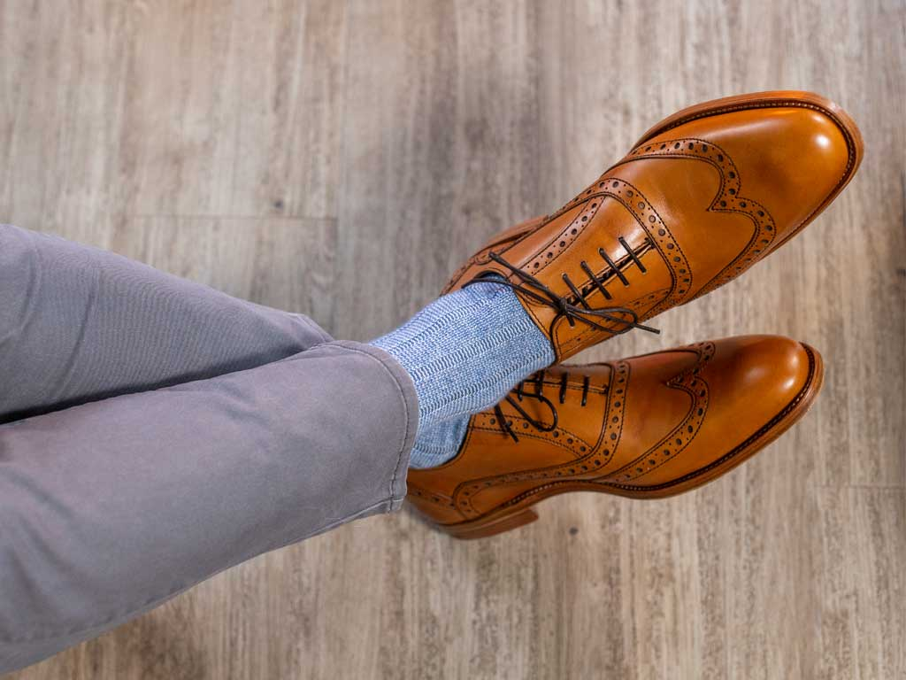 Man wearing blue/grey cashmere socks with tan coloured oxford brogue shoes