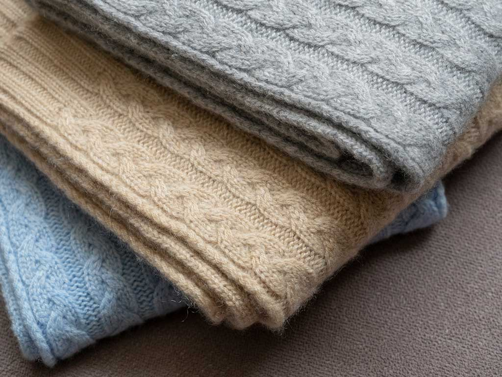 A selection of super soft, cosy cable cashmere scarfs in light blue, neutral and light grey