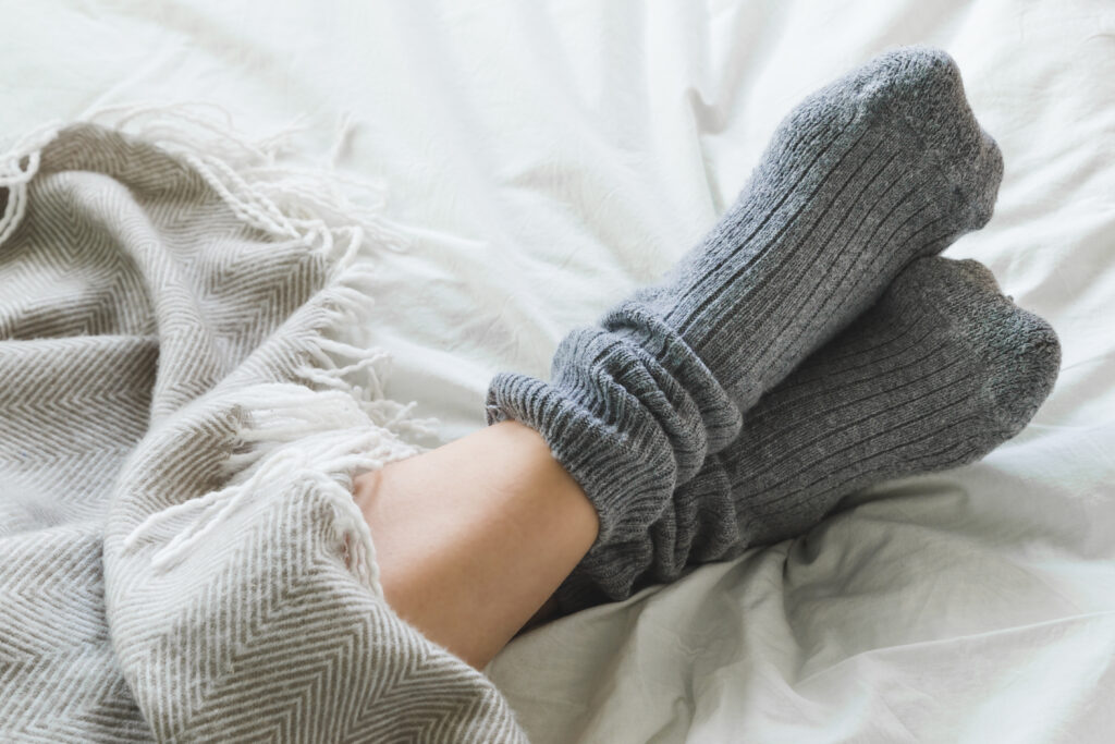 feet crossed with gray socks on bed under blanket